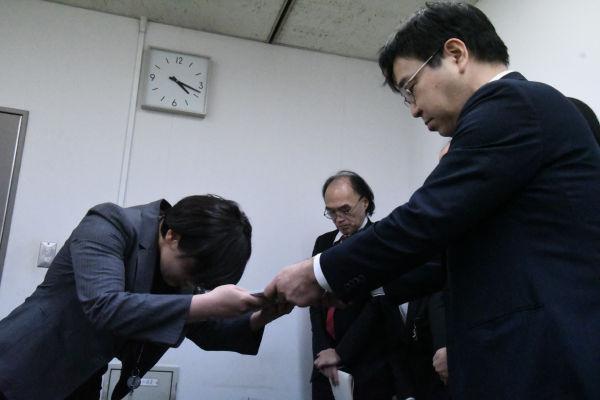 新垣課長補佐(左)は生活保護の引き下げを撤回するよう求める要望書を恭しく受け取ったが・・・。右は厳しい表情の森弁護士。=27日、厚労省 撮影:筆者=