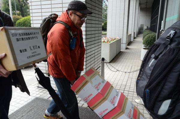 前回(2013年)、生活保護の引き下げに反対する署名10万2,101筆が厚労省に持ち込まれた。=2013年1月、厚労省玄関 撮影:筆者=