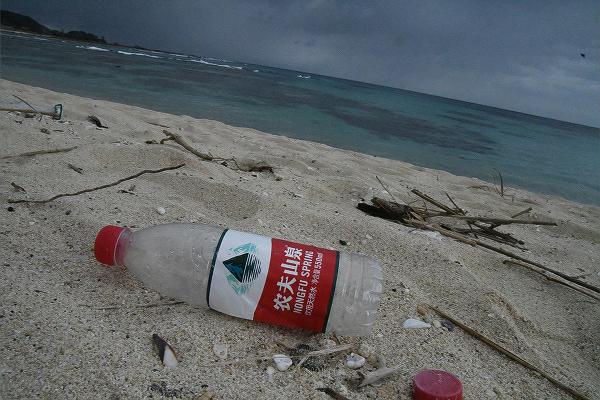 漂着した中国語ラベルのボトルは、海流が東シナ海から奄美大島に向かって流れていることを示す。=10日、奄美大島・土盛海岸 撮影:田中龍作=