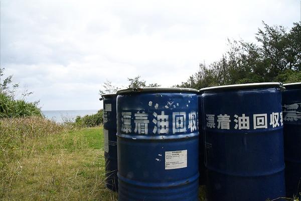 海岸入り口に並んだ漂着油回収用のドラム缶。環境汚染が紛れもなく起きたことを証明する。=10日、奄美大島・土盛海岸 撮影:田中龍作=