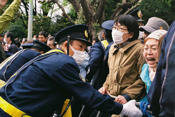 女性(右端)はバリケードを倒そうと懸命に試みたが、高齢のため腕力がなかった。この直後、若い力が後押しし鉄柵は倒れた。=14日、国会議事堂前 撮影:取材班=