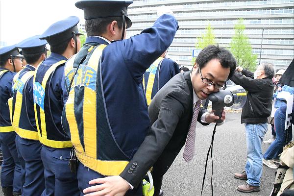 警察から歩道を完全に塞がれないよう、自らの体を割って入れる弁護士。おかげでデモ参加者は会場に入ることができた。弁護士が来る前、警察は完全に塞ごうとした。=14日、国会議事堂前 撮影:筆者=