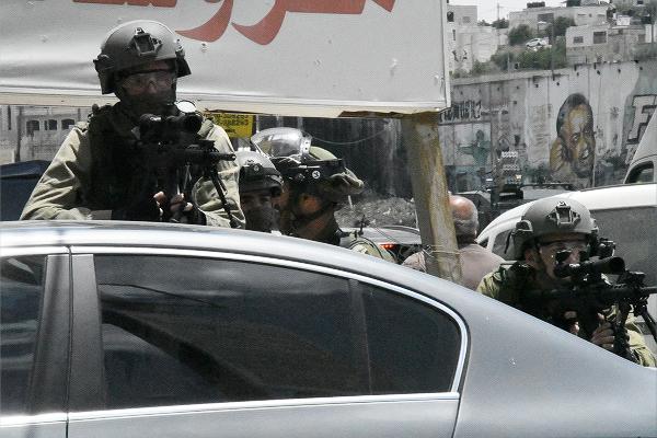 スコープをのぞき照準を合わせるイスラエル軍。=14日、西岸側イスラエル国境 撮影:田中龍作=