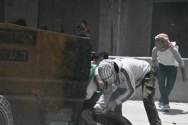 少年たちは鉄製の巨大ゴミ箱を弾除けにしながら前進して行った。=14日、西岸側イスラエル国境 撮影:田中龍作=