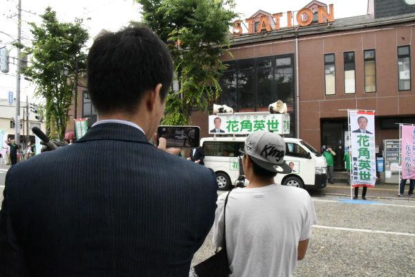 自公陣営の運動員はアツシ(前方Tシャツ)の背後にぴったりと付き、アツシの姿とツイキャス中継画像を録画した。アツシも運動員も田中が後ろから撮影していたことを知らない。=9日、新潟市内 撮影:筆者=
